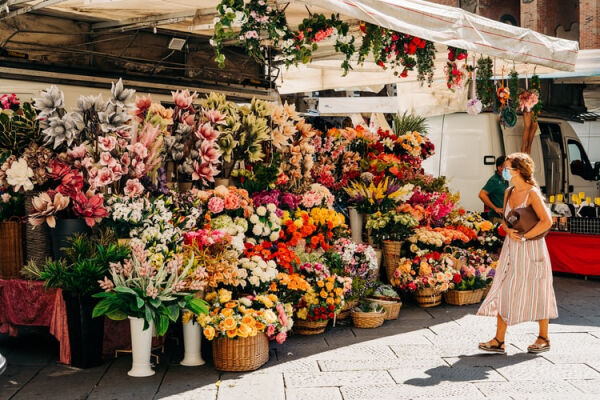 A person standing next to a display of flowers