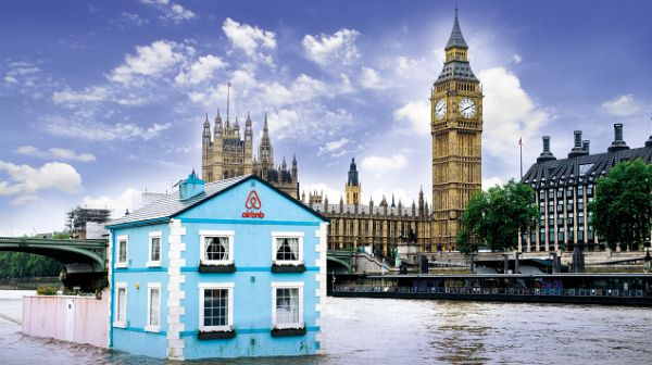 A blue houseboat on the River Thames with Big Ben in the background