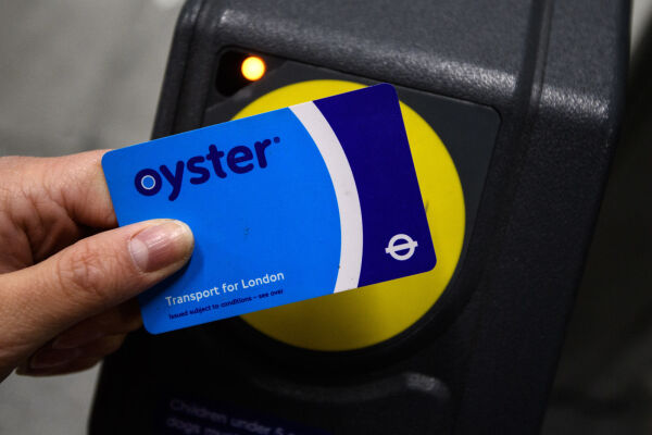 A hand holding an Oyster Card