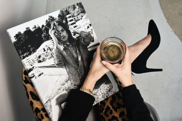 A picture of a woman holding a coffee and a magazine